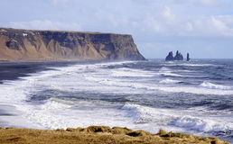Iceland headland. With ocean, rocks, mountains, big waves in ocean, sea stacks black sand beach Stock Image