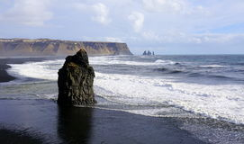 Iceland headland. With ocean, rocks, mountains, big waves in ocean, sea stacks black sand beach Stock Photography