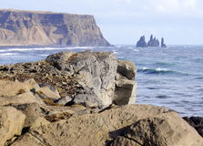 Iceland headland. With ocean, rocks, mountains, big waves in ocean, sea stacks black sand beach Royalty Free Stock Image
