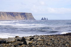 Iceland headland. With ocean, rocks, mountains, big waves in ocean, sea stacks black sand beach Royalty Free Stock Photo