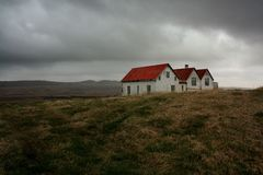 Iceland houses. Old houses on Iceland, under dark clouds in tundra.   Farm white houses with red roof, on solitude Stock Photography