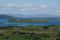 Iceland Lake Myvatn with some islands. Iceland Lake Myvatn with some green islands in the distance from the snow-capped mountains royalty free stock photography