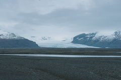 Iceland landscape photography. Glacier in the background coming into the valley from the snowy mountains Royalty Free Stock Photography