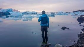 Iceland - m?ody cz?owiek pozycja na skale przy lodowiec lagun? obraz stock