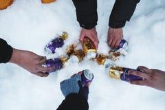 ICELAND - 4 MAR - ręki podnosi puszki zimnego piwa marznięcie w śniegu w zimie dla wiszącego out z przyjacielem w zima wakacje pr Obrazy Stock