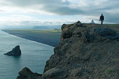 Iceland, Northern Europe. A man walking on the promontory of Dyrholaey with the lighthouse on background on August 18, 2012. The promontory of Dyrholaey is royalty free stock photo