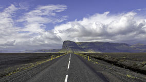 Iceland ring road at Lomugnupur. Straight road through volcanic wasteland heading towards escarpment in the distance under dramatic cloudscape stock photos