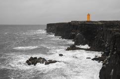 Iceland lighthouse. Orange lighthouse on the black rock cliff  of western Icelandic coast, Snaefellsnes Peninsulain, Iceland Royalty Free Stock Photography