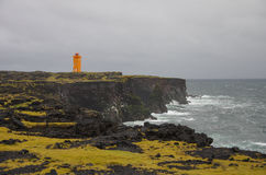 Icelands lighthouse. Orange lighthouse on a rocky beach in Iceland Stock Photo