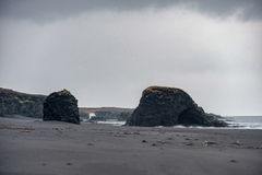 Iceland Seashore with Black sand on beach and rocks. Waterfall in Background. Iceland Seashore with Black sand Royalty Free Stock Image