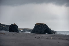 Iceland Seashore with Black sand on beach and rocks. Waterfall in Background. Iceland Seashore with Black sand on beach Stock Photography