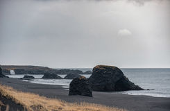 Iceland Seashore with Black sand on beach and rocks. Waterfall in Background Royalty Free Stock Photos