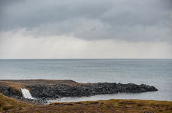 Iceland Seashore with Black sand on beach and rocks. Waterfall in Background with Cloudy Sky. Iceland Seashore with Black sand on beach Stock Photography