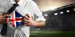 Iceland soccer or football supporter showing flag. Under his business shirt on stadium royalty free stock photography