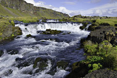 Iceland stream with waterfall. Waterfall along stream at the foot of cliffs with blue cloudy sky royalty free stock photos