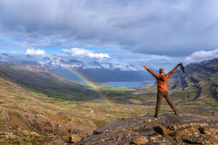 Iceland. Tourist on a Iceland landscape background with fjord and rainbow royalty free stock image