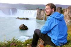 Iceland tourist relaxing by waterfall Godafoss Stock Photos