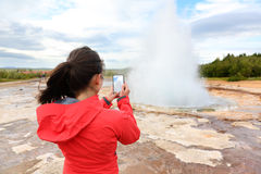 Iceland tourist taking photos of geyser Strokkur. Woman visiting famous tourist attractions and landmarks on the Golden Circle. Girl on holiday vacation Stock Images