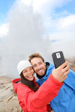 Iceland tourists selfie photo by Strokkur geyser. Couple happy visiting famous tourist attractions and landmarks on the Golden Circle. Multiracial travel Stock Images