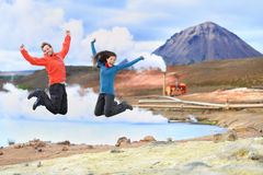 Iceland travel people jumping of joy in nature. Iceland travel people jumping of joy in front of hot spring and geothermal energy power plant in Námafjall in Stock Image