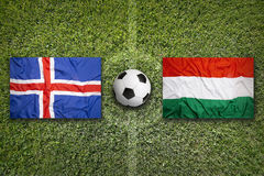 Iceland vs. Hungary flags on soccer field. Iceland vs. Hungary flags on green soccer field Stock Photos