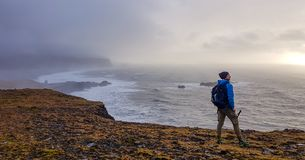 Iceland - Young man standing on a cliff royalty free stock photography