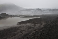 Icelander glacier. A striking glacier between the dark volcanic gound and the fog Royalty Free Stock Photos