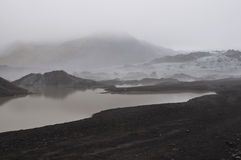 Icelander glacier. A striking glacier between the dark volcanic gound and the fog Royalty Free Stock Photo