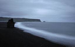 Icelandic black beach. Black beach and volcanic rock formations in water, near Vik, Iceland Royalty Free Stock Photo
