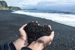 Icelandic black sand held in a man`s hands, resembling a heart. Black sand beach near Vik, Iceland Stock Image