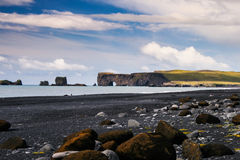 Icelandic black seaside and rock arch - Dyrholaey. One of the black volcanic and quiet beaches of Iceland, with a natural rock arch Stock Photography