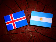 Icelandic flag with Argentinian flag on a tree stump isolated Royalty Free Stock Photos