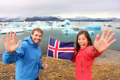 Icelandic flag - tourists on Jokulsarlon, Iceland. On travel. Tourist couple happy holding showing Icelandic flag in front of the glacial lake / glacier lagoon Stock Photo