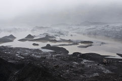 Icelandic glacier. A striking glacier between the dark volcanic gound and the fog Stock Photos