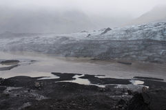 Icelandic glacier. A striking glacier between the dark volcanic gound and the fog Royalty Free Stock Photography