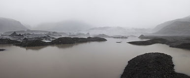 Icelandic glacier. A striking glacier between the dark volcanic ground and the fog Stock Photography