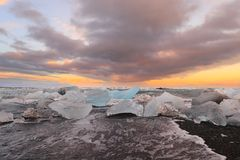 Icelandic glacier Jokulsarlon with icebergs on the beach. At sunset Royalty Free Stock Photography