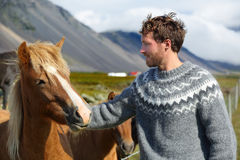 Icelandic horses - man petting horse on Iceland. Man in Icelandic sweater going horseback riding smiling happy with horse in beautiful nature on Iceland Royalty Free Stock Photography