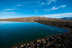 Icelandic lake on a sunny day. With clouds reflected on the surface Stock Photos