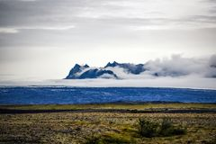 Icelandic landscape, green slopes and mountains in the foggy sum Royalty Free Stock Images