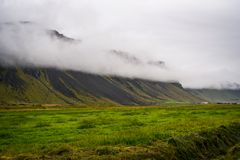 Icelandic landscape, green slopes and mountains in the foggy sum Stock Images