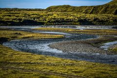 Icelandic landscape, lava fields covered with moss and stream in Royalty Free Stock Image
