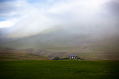 Icelandic Landscape: Lonely House in Foggy Mountains Stock Photo
