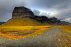 Icelandic Mesa. A dark mesa stands above an orange and yellow landscape and a rock road in Iceland Royalty Free Stock Photography