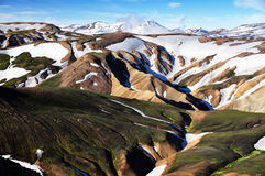 Icelandic mountain landscape on early summer. Icelandic mountain volcanic landscape partly covered by snow with fumarole in background Stock Image