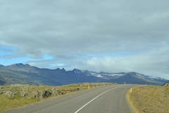 Icelandic mountain stones and road. And sky Royalty Free Stock Photos