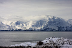 Icelandic mountains with dirty snow. Pile of dirty snow in winter with beautiful wispy clouds drifting over mountains in background across the fjord. Husavik royalty free stock image
