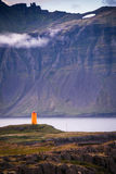 Icelandic orange lighthouse. In Iceland, there are orange lonely lighthouses along the coast. The photo was taken in the eastern fjords Stock Image