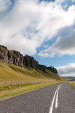Icelandic Road. Stretch of road bordered by mountains in Iceland Stock Photo