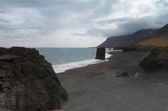 Icelandic shoreline panorama. Horizontal view of an Icelandic beach with a huge rock formation in the middle Stock Photo
